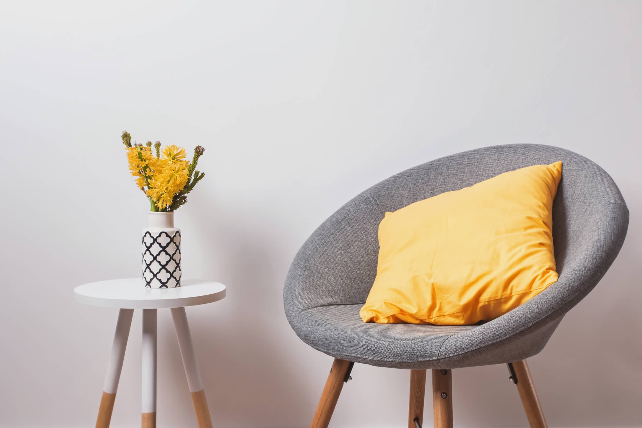 Cozy grey chair with yellow pillow and flowers in the vase standing near the white wall.
